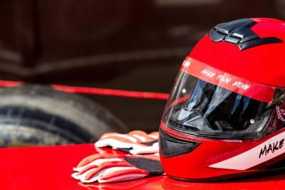 Casque et gants rouges de pilote automobile